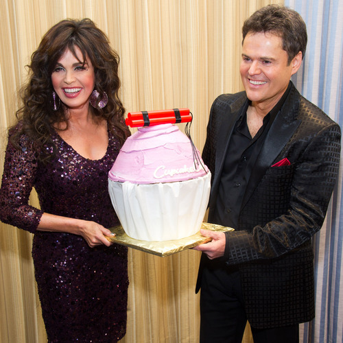 Charles Sykes  |  The Associated Press Marie Osmond, left, presents her brother Donny Osmond with a birthday cake on his 53rd birthday after the opening night performance of 'Donny & Marie - A Broadway Christmas' in New York, Thursday, Dec. 9, 2010.