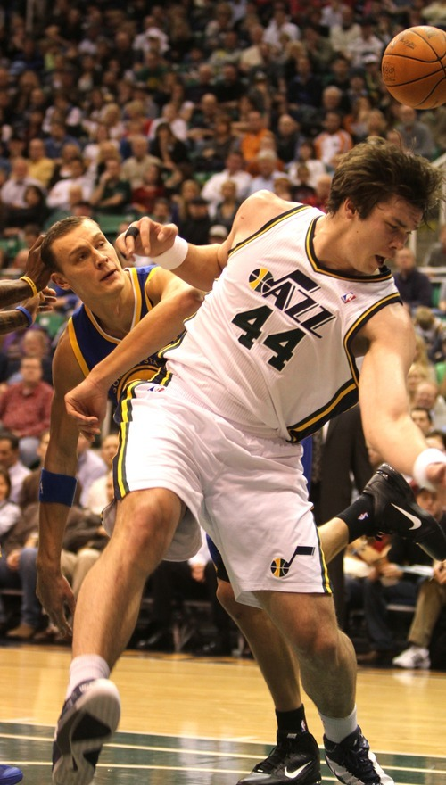 Rick Egan      The Salt Lake Tribune  Utah Jazz center Kyrylo Fesenko (44), is fouled by Golden State Warriors forward Andris Biedrins (15), in NBA action, Utah Jazz vs. The Golden State Warriors,  Monday, December 13, 2010