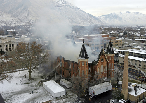 Rick Egan   |  The Salt Lake Tribune  Provo firefighters shoot water on the flames on the north side of the Provo Tabernacle, Friday, Dec. 17, 2010. A painting of Jesus had been badly scorched in the blaze -- save for Christ's image, which was left nearly untouched by the flames. Some considered this a miracle.