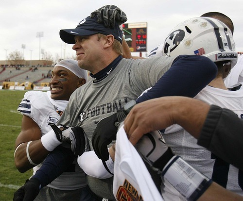 Trent Nelson  |  The Salt Lake Tribune BYU defensive back Brian Logan (7) and other players surround BYU coach Bronco Mendenhall as time runs out and BYU defeats UTEP in the New Mexico Bowl, college football Saturday, December 18, 2010 in Albuquerque, New Mexico.