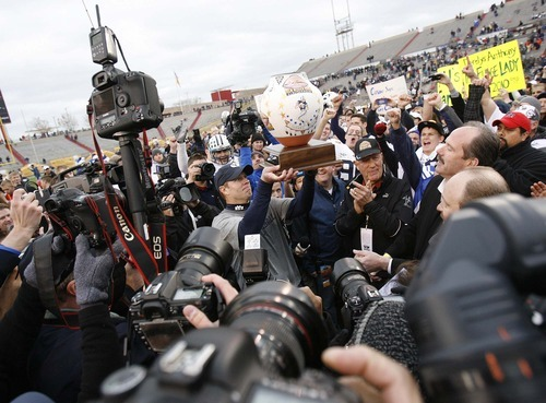 Trent Nelson  |  The Salt Lake Tribune BYU coach Bronco Mendenhall holds the New Mexico Bowl trophy as BYU defeats UTEP in the New Mexico Bowl, college football Saturday, December 18, 2010 in Albuquerque, New Mexico.