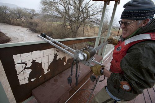 James Howells, a hydrologic technician with the U.S. Geological Survey, lowers a flow meter attached to a torpedo shaped weight from a bridge into the waters of the Virgin River to test the flow and depth of the muddy water rushing through the river Monday in Virgin, Utah. According to the USGS, the Virgin River's peak flow was just under 7000 cubic feet per second on Monday and the river was nearly two feet above flood stage. Jud Burkett / The Spectrum