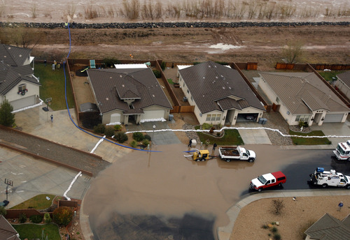 Rick Egan   |  The Salt Lake Tribune  Residents pump water from the street in front of their home in Saint George, Tuesday, December 21, 2010