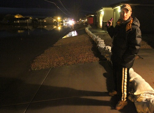 Rick Egan   |  The Salt Lake Tribune  Nathan Barrow checks out the flooding situation near his home in Stonegate subdivision, in Washington, Utah,  Tuesday, December 21, 2010. Crews from Washington City were still pumping the water out of the streets late Tuesday night.