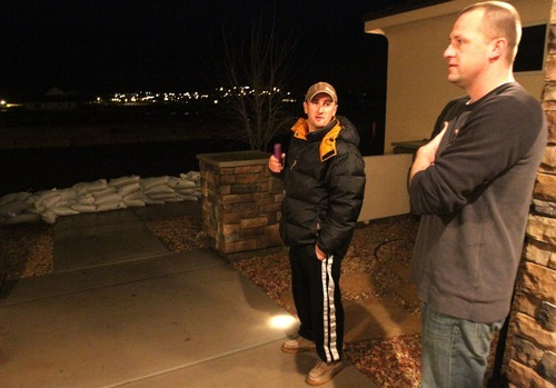 Rick Egan   |  The Salt Lake Tribune  Nathan Barrow (left) and Danny Kemp,(right) check out the situation in their neighborhood, in Stonegate subdivision, in Washington, Utah,  Tuesday, December 21, 2010. Crews from Washington City were still pumping the water out of the streets late Tuesday night.