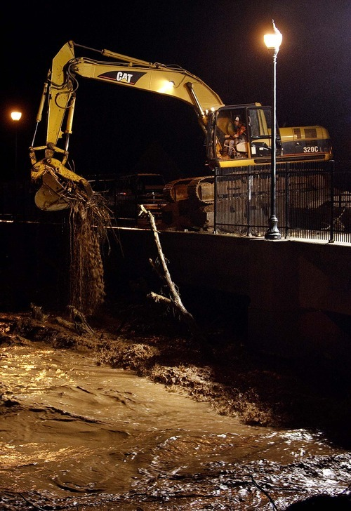 Trent Nelson  |  The Salt Lake Tribune Crews work to remove trees and other debris, from a bridge on Valley View Drive Tuesday, December 21, 2010. Between 12-15 truckloads were taken out as of 8pm.