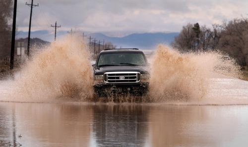 Rick Egan   |  The Salt Lake Tribune  A truck makes its way through the water covering the road, on Highway 56 near Beryl, Utah, Thursday, December 23, 2010