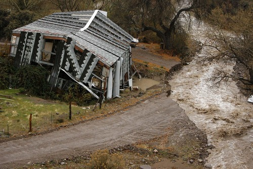 Trent Nelson  |  The Salt Lake Tribune High waters in Beaver Dam Wash in December washed out a road in Motoqua, Utah, next to a structure damaged in the 2005 flooding.