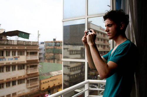 Jeremiah Stettler  |  The Salt Lake Tribune  A.J. Walker stands at the window of his Kampala hotel, snapping photos of the city's commerce-clogged downtown.