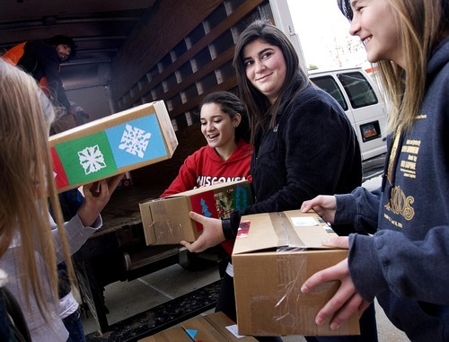 Djamila Grossman  |  The Salt Lake Tribune From left: Juliette Gershan, 15, Maddy Dobkin, 15, and Shannon Tivona, 14, volunteers with the Shalom Salaam Tikkun Olam Christmas Volunteer Service Project, laugh as they pack boxes into a truck at West High School in Salt Lake City on Saturday.