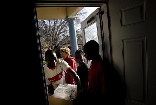 Djamila Grossman  |  The Salt Lake Tribune Grace a Dieu Nodjigoto carries a box of donated items into his family's Salt Lake City home on Saturda. The family from the Central African Republic received food, clothing and toys from volunteers with the Shalom Salaam Tikkun Olam Christmas Volunteer Service Project.