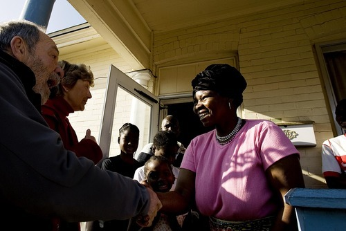 Djamila Grossman  |  The Salt Lake Tribune Esther Nodjigoto shakes hands with Stan Herskovitz, a volunteer, as her family watches in the back, after Herskovitz and his wife Pam delivered food and other donations to their Salt Lake City home on Saturday. The family from the Central African Republic was one of over 100 refugee families who received food, clothing and toys from volunteers with the Shalom Salaam Tikkun Olam Christmas Volunteer Service Project.