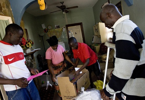 Djamila Grossman  |  The Salt Lake Tribune  Esther Nodjigoto with her son Nairobi, 15, unpack boxes filled with donations, as her other son Grace a Dieu and husband Benjamin watch, at their Salt Lake City home, Saturday, Dec. 25, 2010. The family from the Central African Republic received food, clothing and toys from volunteers with the Shalom Salaam Tikkun Olam Christmas Volunteer Service Project.