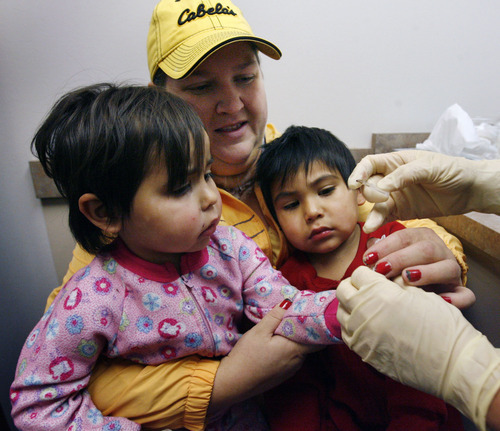 Steve Griffin | The Salt Lake Tribune Heather holds her foster twins, Amerie and Trace Delgado, as Amerie gets her finger pricked by Rosa Curletto at the Weber-Morgan Health Department's WIC clinic in Ogden. Heather is adopting the 2-year-olds and qualifies for the WIC program, a supplemental food and nutrition education program for women, infants and children.