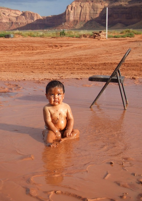 A photo of Mary Begay's grandson Hisae Billah, taken in August 2007 as he plays in the contaminated mud and water that washed out his family's front yard after a heavy rainstorm. Mary Begay realized months later the rainwater that washed off the Oljato Mesa and into her yard where her grandson was playing was, in all likelihood, contaminated as it had washed over the uranium piles lying at the foot of the mesa directly across from her home.  Courtesy photo, Mary Begay