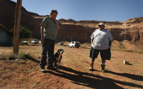 LEAH HOGSTEN | The Salt Lake Tribune Elsie Mae Begay's youngest brother Mark Olds, left, and extended brother-in-law Frank Haycock, right, say they both played around the mine, shown as a white streak on the Oljato Mesa in the background. In 1997, the U.S. Environmental Protection Agency found radiation contaminated homes, water wells and radiation hot spots all over the Navajo reservation.