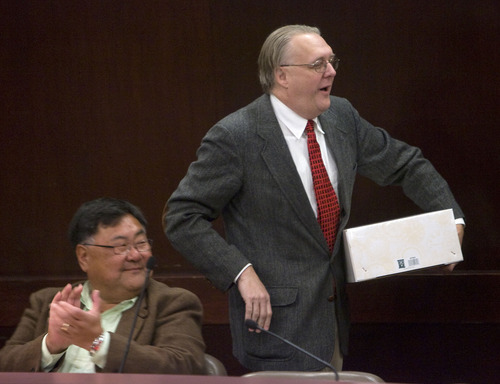 Al Hartmann  |  The Salt Lake Tribune  Outgoing Salt Lake County Council member Joe Hatch leaves the council chambers with his going away gift Monday January 3rd.  Fellow council member Randy Horiuchi, left, applauds.