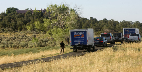 Al Hartmann  |  The Salt Lake Tribune  Federal agents and archaeologists with two moving trucks gather below the Redd home south of Blanding on July 7, 2009 to search for and haul away confiscated artifacts. The  confiscation of the artifactswas part of a plea deal between Jeanne Redd and federal prosecuters.