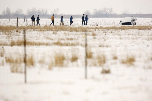 Trent Nelson  |  The Salt Lake Tribune Law enforcement officers investigate a field in Hooper where a man was fatally shot by police after a chase Tuesday, Jan. 4, 2011. Police say the man drove this vehicle into a ditch before he attempted to flee and displayed a gun.