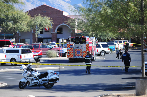 Emergency officials work at the scene of a shooting that authorities claim involved Rep. Gabrielle Giffords, D-Ariz., Saturday, Jan. 8, 2011, at a Safeway grocery store in Tucson, Ariz. (AP Photo/Chris Morrison)