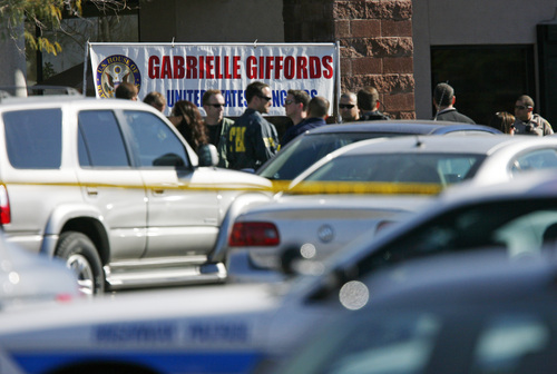 Law enforcement personnel listen to a briefing in Tucson, Ariz., Saturday, Jan. 8, 2011 near the scene of a shooting that involved Rep. Gabrielle Giffords, D-Ariz. (AP Photo/The Arizona Republic, David Kadlubowski)