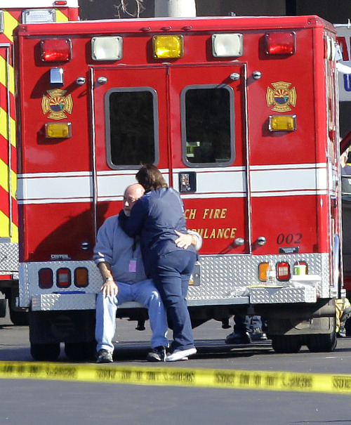 Two people embrace each other at the scene where Rep. Gabrielle Giffords, D-Ariz., and others were shot outside a Safeway grocery store in Tucson, Ariz. on Saturday, Jan. 8, 2011. (AP Photo/Matt York)