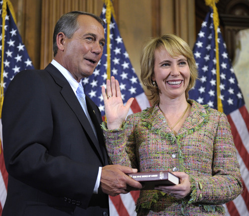 In this January photo, House Speaker John Boehner reenacts the swearing in of Rep. Gabrielle Giffords, D-Ariz., on Capitol Hill in Washington. (AP Photo/Susan Walsh, File)