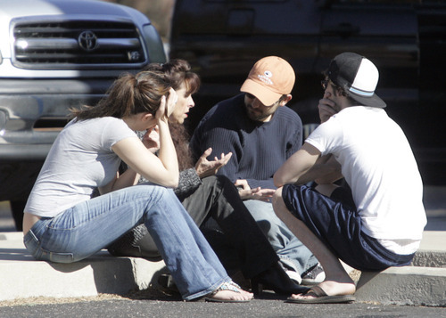 People talk at the scene of a shooting involving Rep. Gabrielle Giffords, D-Ariz., and others on Jan. 8, 2011 in Tucson, Ariz.  (AP Photo/Arizona Daily Star, Dean Knuth)