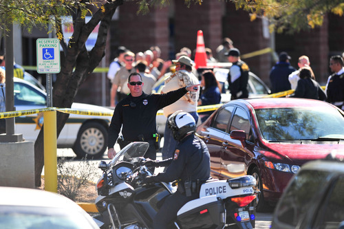 Emergency workers gather at the scene of a shooting involving Rep. Gabrielle Giffords, D-Ariz., and others Saturday, Jan. 8, 2011, at a Safeway grocery store in Tucson, Ariz.  (AP Photo/Chris Morrison)