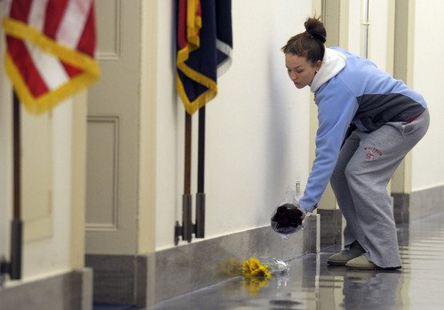 An unidentified woman places flowers near the Capitol Hill office of Rep. Rep. Gabrielle Giffords, D-Ariz., Saturday, Jan. 8, 2011 on Capitol Hill in Washington after Giffords was shot in the head in her district in Arizona Saturday.  (AP Photo/Susan Walsh)