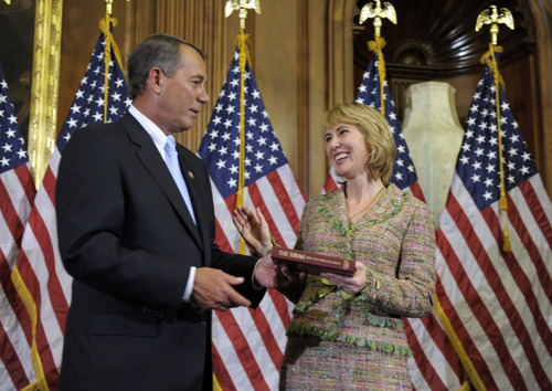 In this photo taken Wednesday, Jan. 5, 2011, House Speaker John Boehner of Ohio reenacts the swearing-in of Rep. Gabrielle Giffords, D-Ariz., on Capitol Hill in Washington. Giffords is in critical condition after being shot in the head in her district in Arizona Saturday, Jan. 8, 2011. (AP Photo/Susan Walsh)