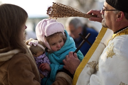 Chris Detrick  |  The Salt Lake Tribune  Father Elias Koucos, of the Prophet Elias Greek Orthodox Church, blesses Oksana Zapassoff and her daughter Katerina, 4, during a water blessing ceremony at Sugar House Park Thursday January 6, 2011.