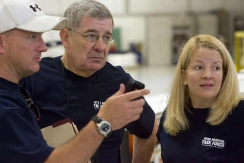 Steve Griffin  |  The Salt Lake Tribune  Stephen Studdert, center, talks with John Nichols and Erin McBride both members of the executive team for the Utah Hospital Task Force, as the group prepares to depart from Million Air in Salt Lake City for Haiti Jan. 28. Doctors and engineers and support staff of over 100 people left on the 21-day humanitarian effort headed by Studdert.
