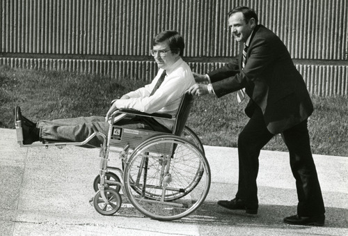 FILE  | The Salt Lake Tribune Mark Hofmann being pushed in wheelchair by his father.