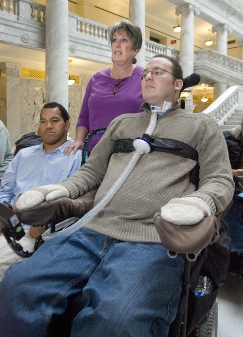 Paul Fraughton  |  The Salt Lake Tribune    At a press conference in the capitol rotunda,Terry Griffin stands behind her son Ryan (right) and Eniketi Fevanga.  As a caregiver to both men, she talked about her experiences and difficulties  dealing with the State of Utah in regards to  receiving  services .  The Disabled Rights Action Committee announced at the conference that it has  filed a complaint with  the justice department  over the state's  non compliance with the supreme court's  Olmsted  decision dealing with the unnecessary segregation  of individuals with disabilities in nursing homes or other institutional  settings.The justice deprtment  is going to investigate the groups allegations. Wednesday,January 12, 2011