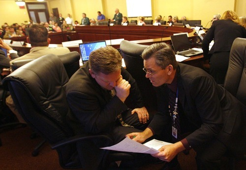 LEAH HOGSTEN | Tribune File Photo Former Rep. Craig Frank, left, and Rep. Ken Sumsion huddle during the last legislative session on the House floor. Frank is fighting to retain his seat, disputing state maps showing he moved outside his district and is disqualified from serving.