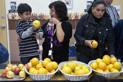 Djamila Grossman  |  The Salt Lake Tribune Maria Barajas gives her son, George Barajas, 4, and orange and a bottle of water, at a nutrition fair she organized at Rose Park Elementary School, Nov. 13, 2010. The fair was intended to educate community members about eating right, diabetes and eating disorders, among others issues.