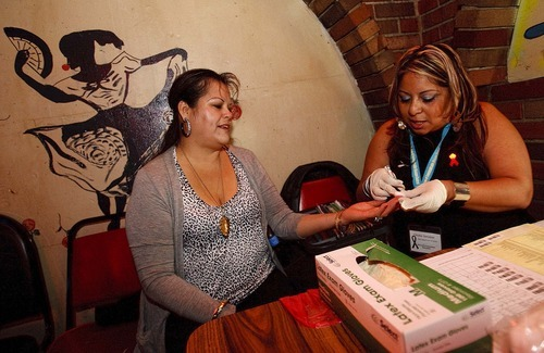 Trent Nelson     The Salt Lake Tribune Claudia Gonzalez of the Utah Department of Health (right) takes a blood sample from Gema Guerrero while offering free HIV tests at the Durango Nightclub in December.