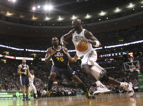 Boston Celtics forward Kevin Garnett, right, drives to the basket against Utah Jazz forward Al Jefferson during the second half of an NBA basketball game in Boston, Friday, Jan. 21, 2011. The Celtics defeated the Jazz 110-86. (AP Photo/Charles Krupa)