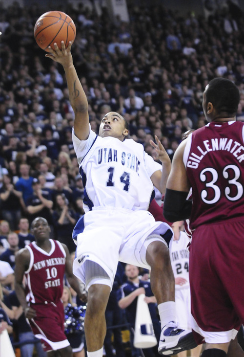 Utah State's E.J. Farris (14) shoots the ball as New Mexico State's Troy Gillenwater (33) looks on during first half of the NCAA men's basketball game at Spectrum Stadium in Logan, Utah on January 22, 2011. (AP Photo/Jennifer Meyers - The Herald Journal)