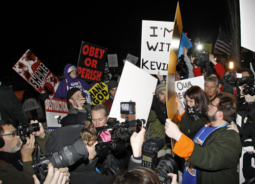 Director Kevin Smith, bottom right, faces off with protestors from the Westboro Baptist Church, rear left, as he arrives at the premiere of his movie