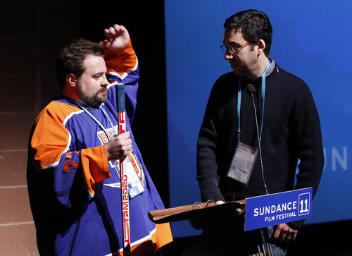 Director Kevin Smith, left, performs a mock auction of his film