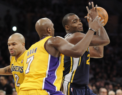 Utah Jazz forward Paul Millsap, right, attempts to get by Los Angeles Lakers forward Lamar Odom (7) and guard Derek Fisher (2) in the first half of an NBA basketball game Tuesday, Jan. 25, 2011, in Los Angeles. (AP Photo/Gus Ruelas)