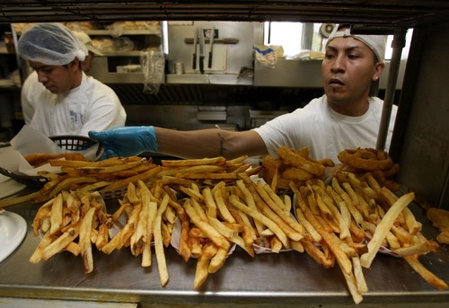 Francisco Kjolseth  |  Tribune file photo Sergio Ortiz, left, keeps busy cranking out burgers while Isaias Castro fills French fry orders during a lunch rush at the popular Hires Big H eatery in Salt Lake City. The restaurant's founder, Don Hale, died Saturday at 93.