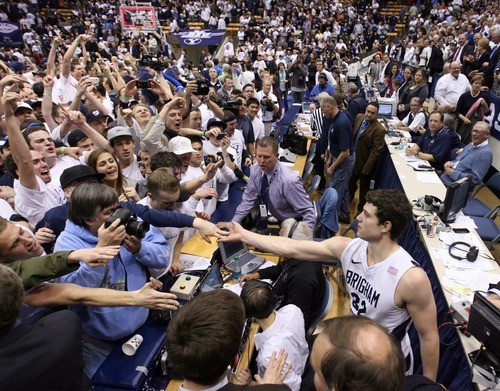 Steve Griffin  |  The Salt Lake Tribune   After the crowd stormed the court BYU guard Jimmer Fredette is protected from the screaming fans behind the scorer's table following BYU's victory over San Diego State men's basketball game at the Marriott Center in Provo Wednesday, January 26, 2011.