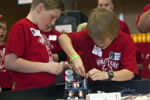 Chris Detrick  |  The Salt Lake Tribune Red Cross Robots' Walker Vincent, left, and Jonathan Brucks, prepare the robot for competition during the Utah First Lego League Championship at the University of Utah in January. Fifty-six junior-high-aged teams, 560 total kids, from across the state competed in contests using Lego robots they built.