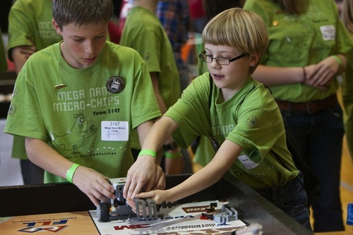 Chris Detrick  |  The Salt Lake Tribune Mega Nano Micro Chips' Soren Selph, 10, left, and Noble Melton prepare the team robot for competitio.