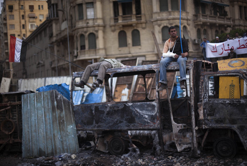 Anti-government protestors are seen atop burnt out vehicles during clashes in Cairo, Egypt, Thursday, Feb. 3, 2011. Protesters and regime supporters skirmished in a second day of rock-throwing battles at a central Cairo square while new lawlessness spread around the city. (AP Photo/Emilio Morenatti)