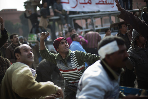 Egyptian anti government protesters throw stones during clashes in downtown Cairo, Egypt, Thursday, Feb. 3, 2011. New clashes are heating up again and shots are being fired in the air around Cairo's central Tahrir Square as anti-government protesters push back regime supporters.  The two sides are trading volleys of stone-throwing, but government backers are falling back and protesters are swarming onto a highway overpass from which their rivals had pelted them with stones and firebombs overnight. (AP Photo/Emilio Morenatti)