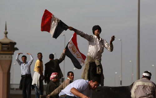 An anti-government protester swings an Egyptian flag, while smoking a cigarette, to beckon others to reinforce those at the frontline of clashes with pro-government supporters, near the Egyptian Museum in downtown Cairo, Egypt, Thursday, Feb. 3, 2011. Protesters and regime supporters skirmished in a second day of rock-throwing battles at a central Cairo square while new lawlessness spread around the city. (AP Photo/Ben Curtis)